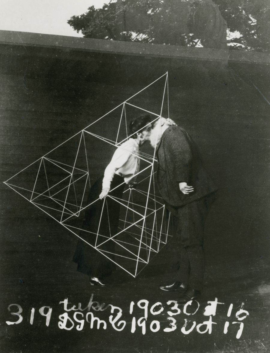 Alexander Graham Bell and Mabel kissing within a tetrahedral kite.
